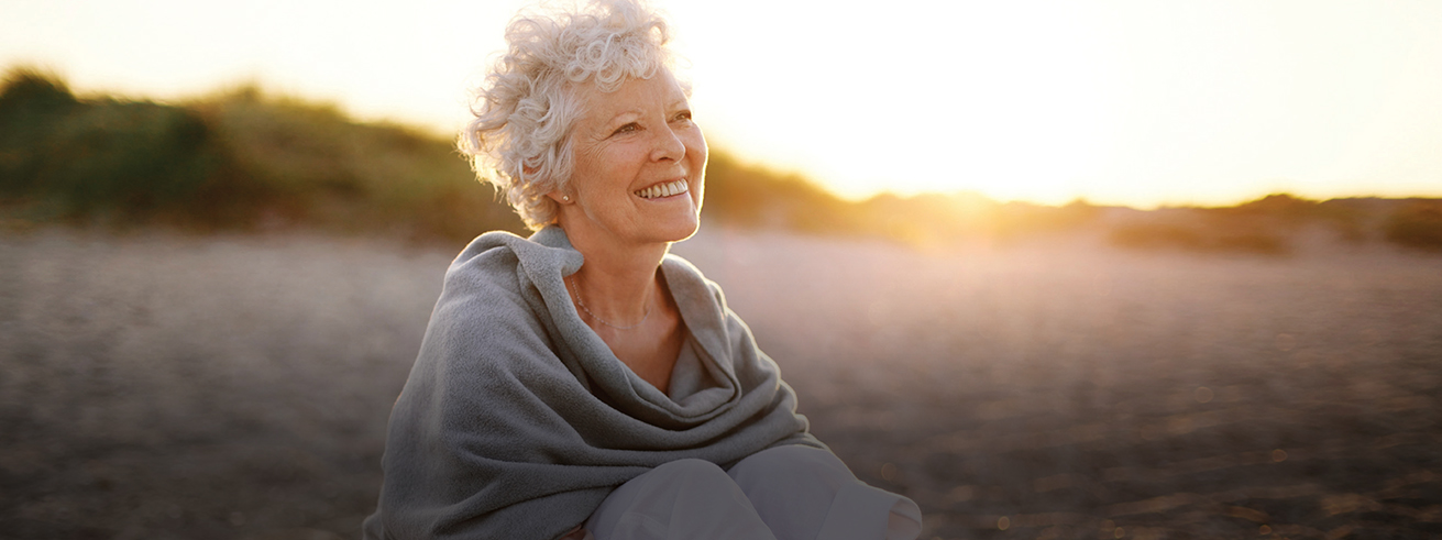 Female senior sitting on the beach smiling looking ahead in the distance with the sun in the horizon