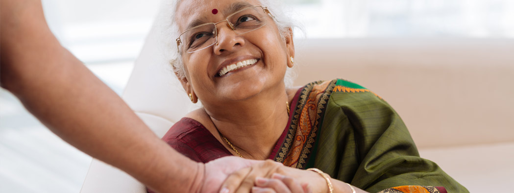 Female senior looking up smiling shaking an individual's hand indoors